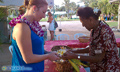 Valarie and Aunty Helen weave ti leaves with plumeria to make an ankle bracelet.
